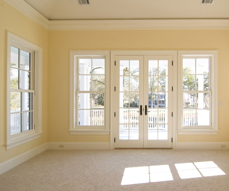 A room with yellow walls, white trim and neutral carpet. Sunlight streams in through energy-efficient custom windows and a set of French-style patio doors.