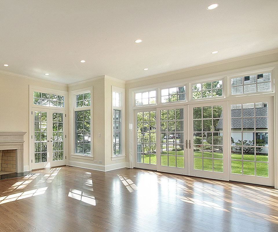 A sunlit room with tan walls, a fireplace and luxurious wood floors. Light streams in through floor-to-ceiling energy-efficient windows, and two sets of French-style patio doors.