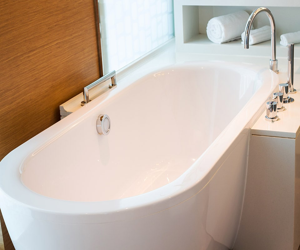 A beautiful and durable deep tub in white, with chrome fixtures, in a bright, richly paneled bathroom