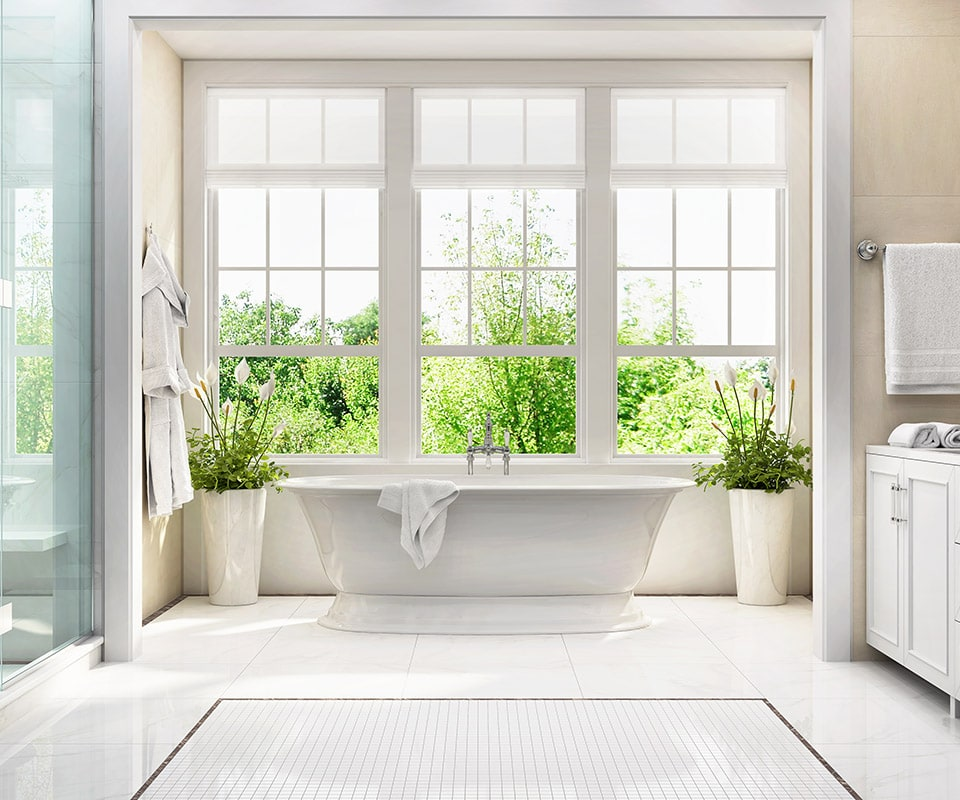 A bright updated bathroom. There is a large bank of windows with landscaping outside. We see an elegant glass shower door to the left. A large, deep, white soaking tub is at center, right by the window, and plants in large white pots flank it. The floor is laid out in premium white tile and mosaic, the walls are a neutral tan, and a whit vanity with chrome fixtures is visible to the right.