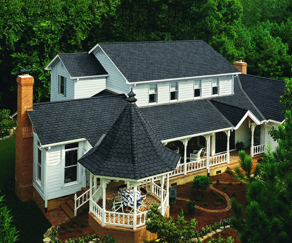 A white house with high quality roof of black Certainteed shingles. The property includes a shingled gazebo, landscaping and beautiful woods.