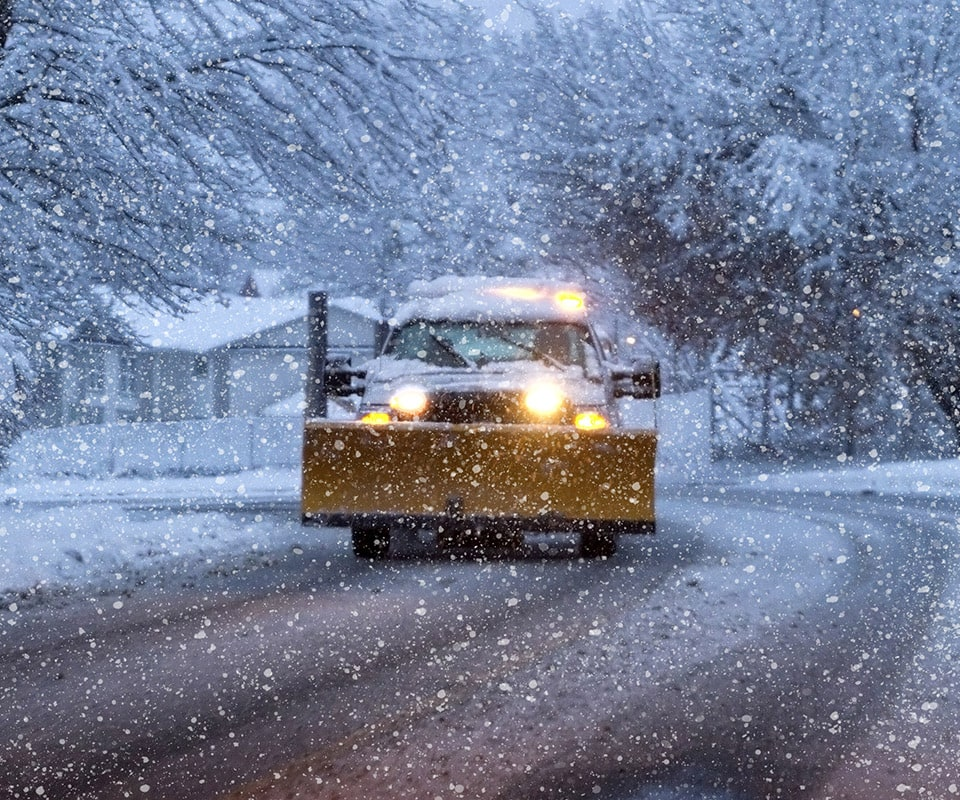 A white truck with a yellow plow travels down the road during a snowstorm. Its lights are on. When you need a snow removal service, give us a call for reliable, prompt service.