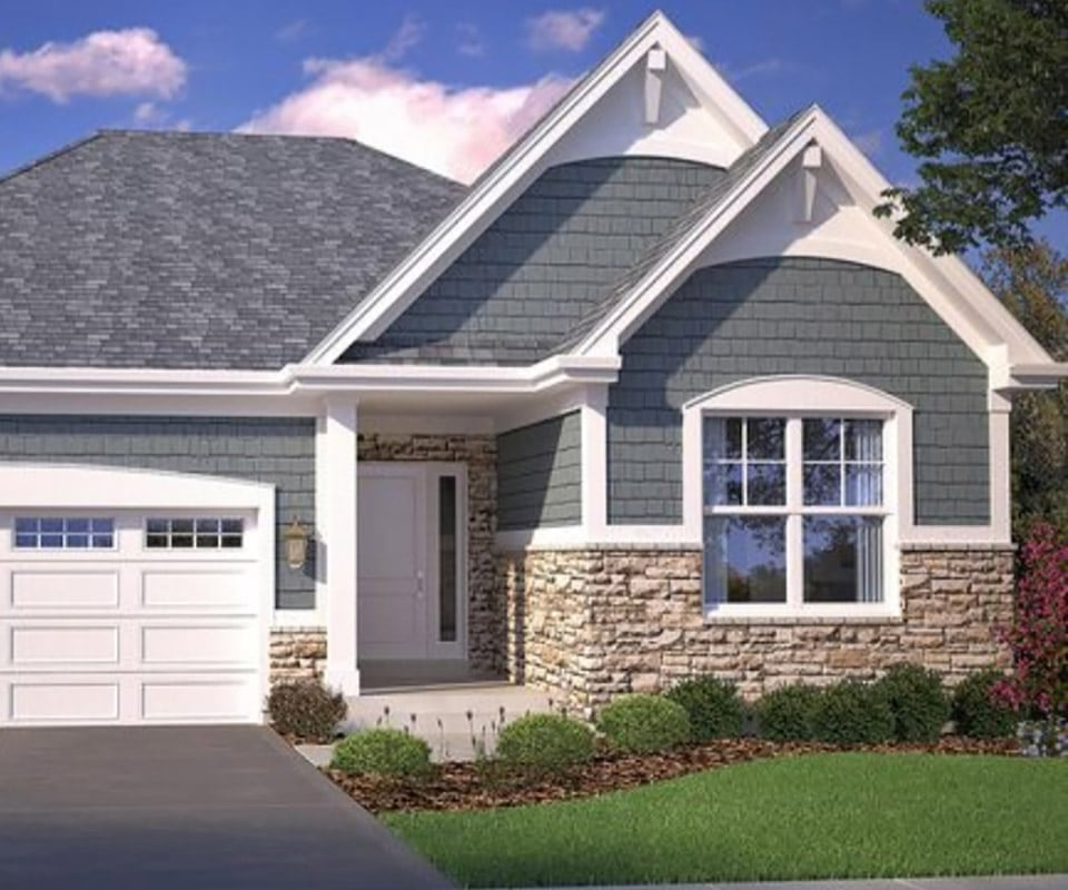 A beautiful house with gray siding, white trim, and excellent stonework. To get your own beautiful, durable siding, call today for a free vinyl siding cost estimate.